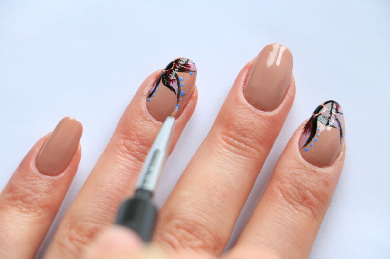 """6. Follow the line of the petals, while dotting with H&M Nail Polish in """"Sky High""""."""