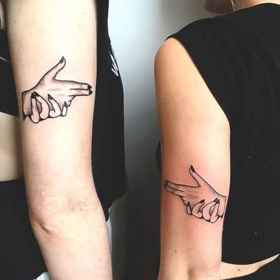 gun point tattoo fingers