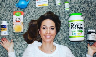 saarah wassel samadani in a white shirt laying down on a gray carpet with products around her head. the products are enzymedica digest gold, pacific bone broth, nettipot in blue, boiron oscillococcinum, hyperbiotics pro-15, orgain organic protein power and manuka honey