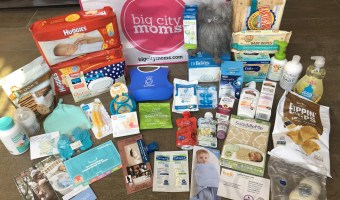 giftbag from biggest baby shower includes a white bag with a pink logo, huggies dipers in red packaging, huggies wipes in blue and white polkadots, mrs thinsters chocolte chip cookies, smarty pants vitamin with a teal top, a mam yellow toothbrush, a teal beanie, baby bjorn blue hard bib with white pearls, nm squares in reen packaging, ellas organic in a red pouch, kabrita goats milk baby food in a white package, swaddleme swaddle in giraffe print, palmers lotions in white packaging, mam nottle, dapple dish soap, babyganics alcohol-free hand sanitizer, earths best baby wipes and diapers, dr browns bottle, and a gray owl biggest baby shower la