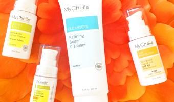 MyChelle skincare items on orange petals.