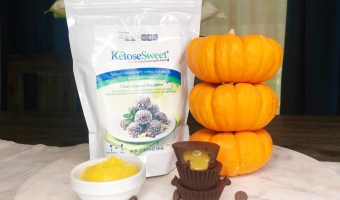 stacked chocolate covered pumpkin cups next to ketose sweet sweetener package and three small orange pumpkins stacked.