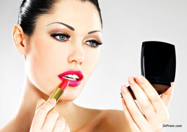 Beautiful woman applying pink lipstick on lips