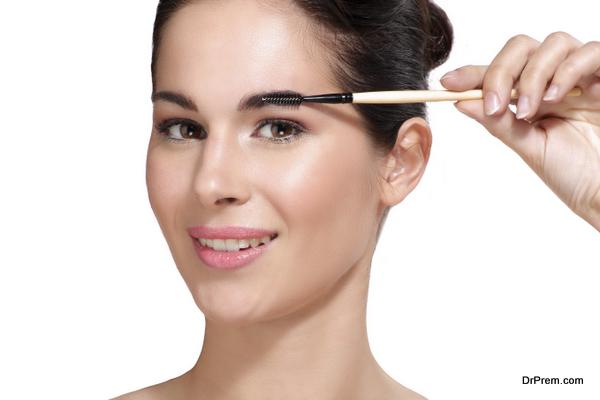 Beautiful young woman applying eyebrow brush