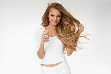 kobieta spryskuje swoje włosy preparatem