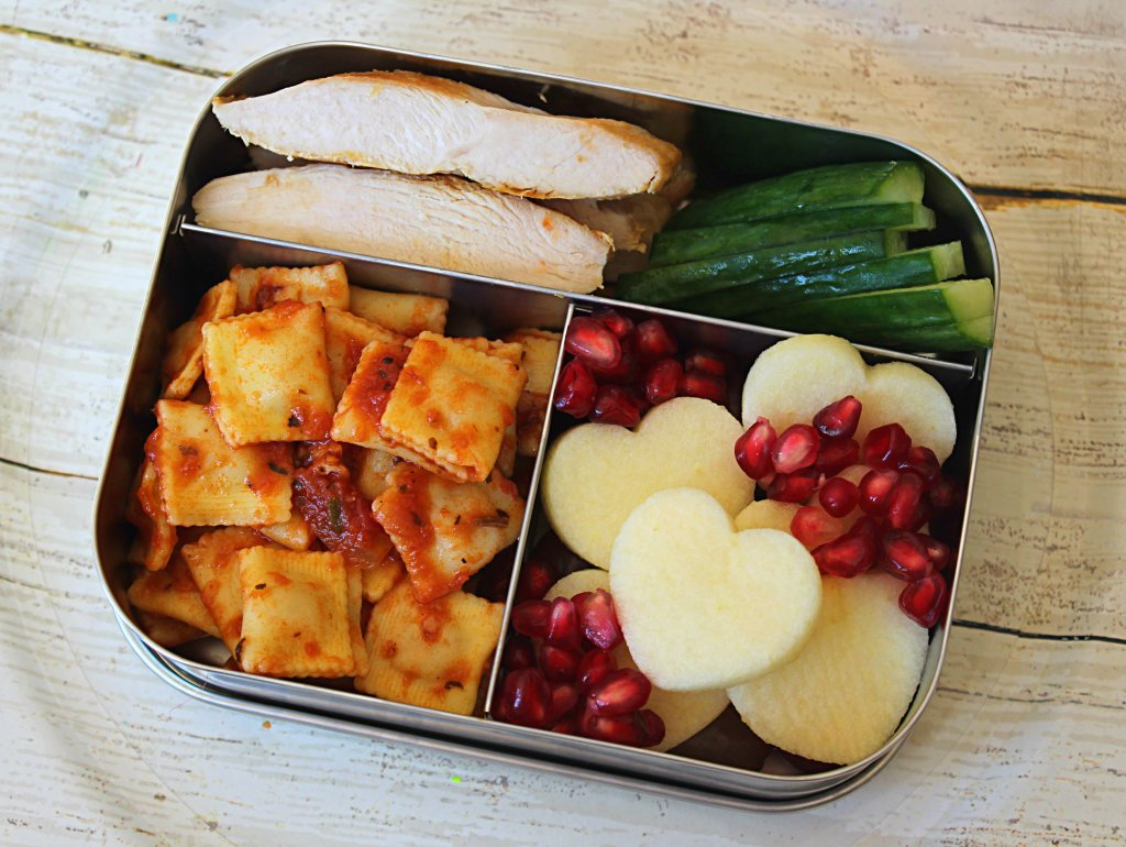 Healthy Kids Bento box lunch ideas: ravioli, grilled chicken breast, cucumbers, apple and pomegranates