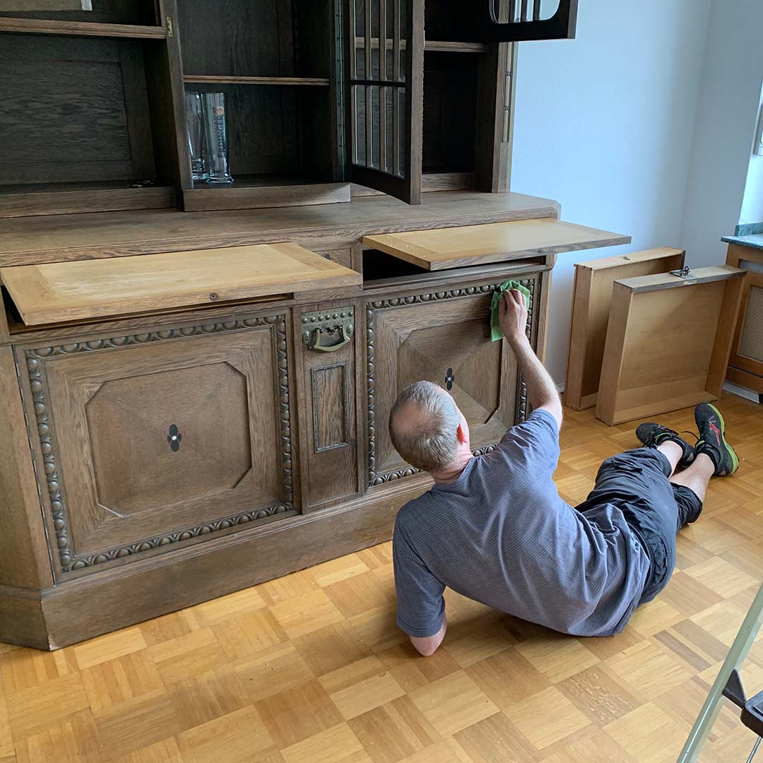 Der Mann reinigt die Kredenz