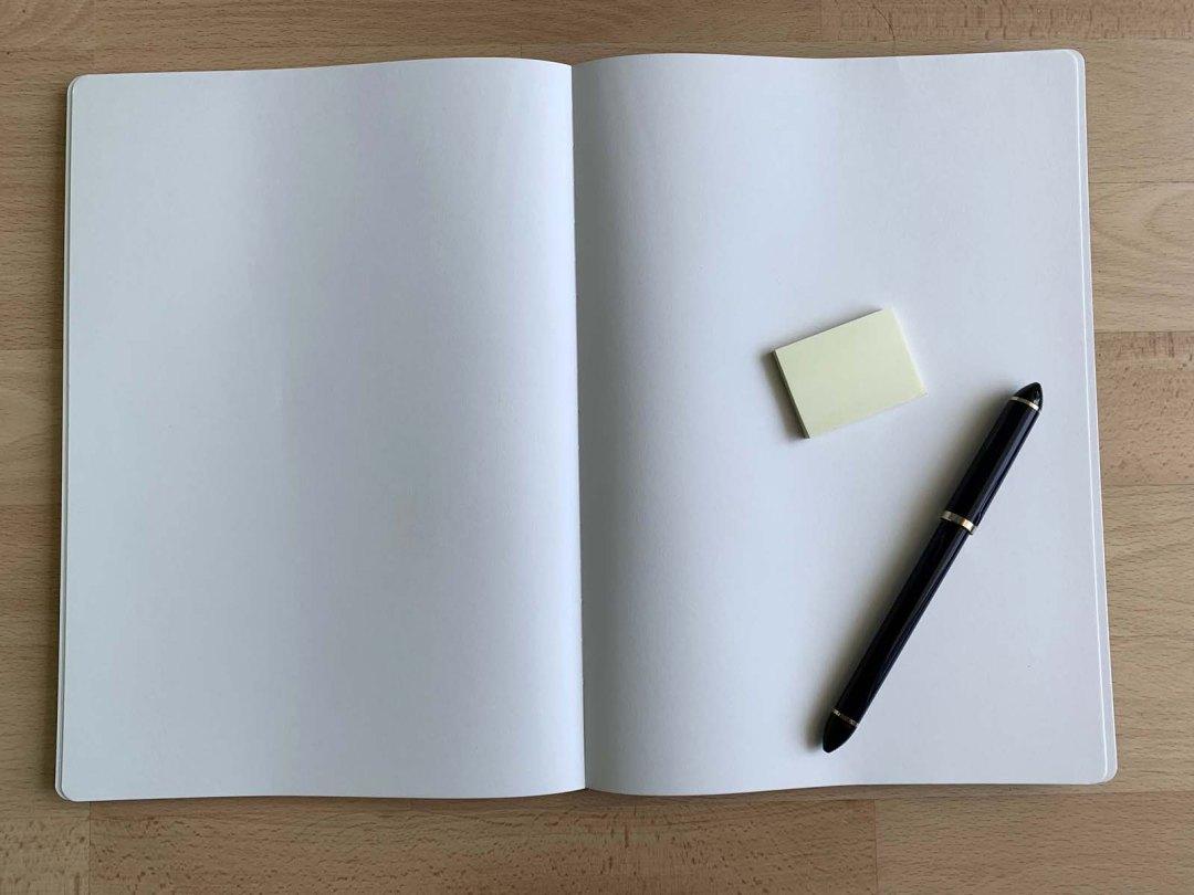 Notizbuch, Klebezettel und Stift für einen sortierten Aufgabenspeicher