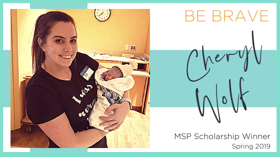 scholarship winner, cheryl wolf, holding a newborn baby