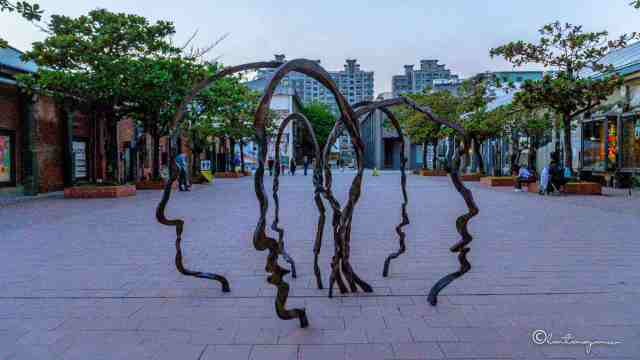 sculpture of man and woman faces in a park in kaoshiung taiwan