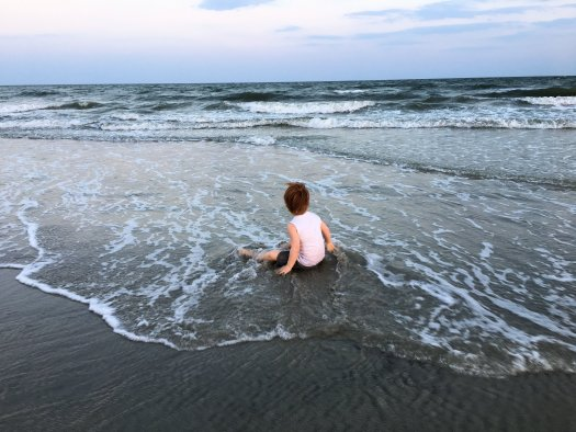 My son sitting in the surf, looking out at the vast and beautiful ocean.
