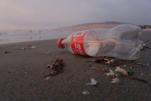 Empty Coca-Cola bottle lying on the beach