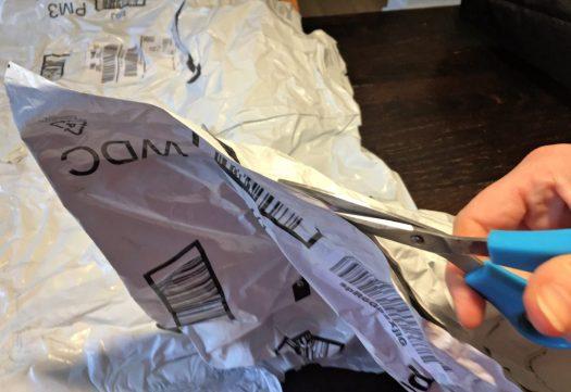 Cutting up plastic white Amazon shipping envelopes