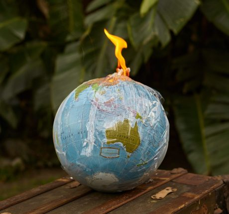 Photo of globe wrapped in plastic film and on fire.