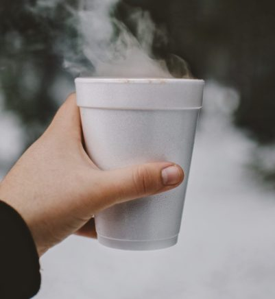 Hand holding a Styrofoam/ploystyrene cup with steam coming out of it.