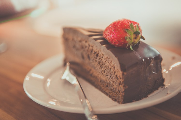 A slice of chocolate cake, with a strawberry on top, sitting on a white plate with a fork