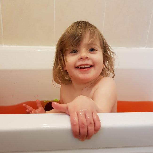 Smiley toddler girl in bathtub full of slime