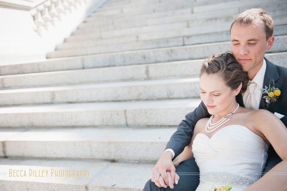 couple sitting on steps of madison capitol building for portraits on wedding day