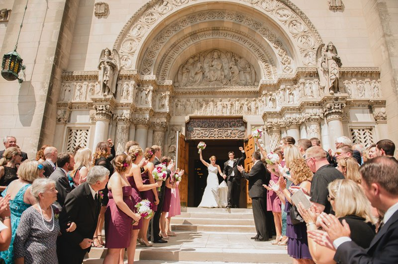 bride and groom exit church with clapping crowd