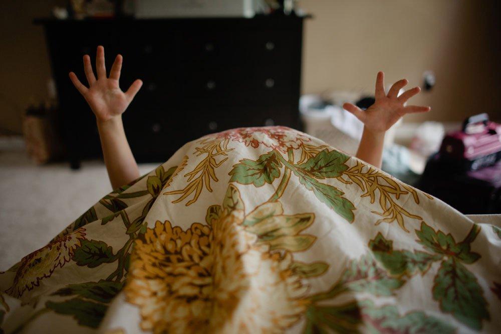ringbearer playing under blanket