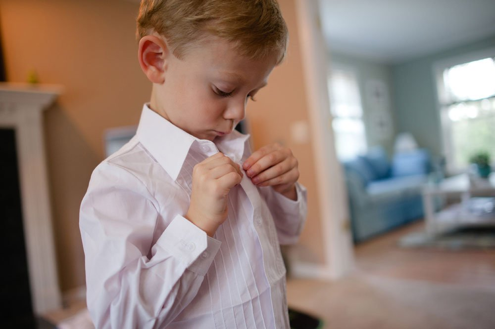 ringbearer buttoning own shirt