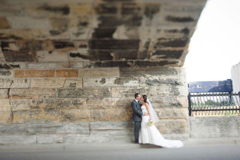 bride and groom at stone arch bridge minneapolis