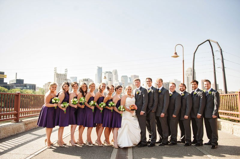 bride and groom with large wedding party at stone arch bridge minneapolis wedding photographer