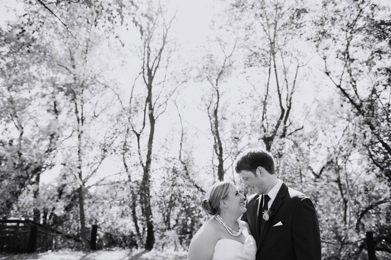 bride and groom among trees at stone arch bridge minneapolis wedding photographer