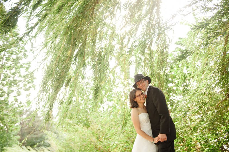 bride and groom under willow tree blowing in wind on Lake Hiawatha for Minneapolis wedding