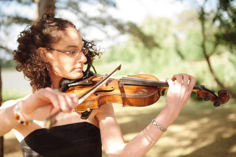 bride's sister plays violin before wedding ceremony at Lake Hiawatha