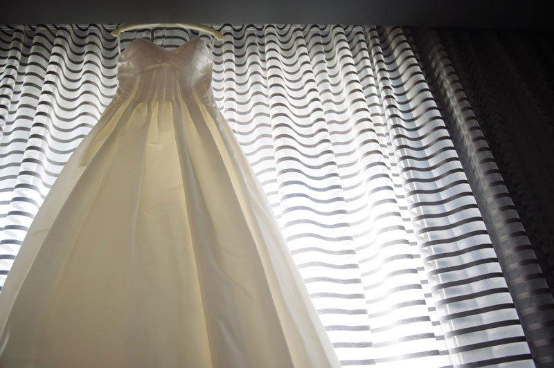minneapolis wedding photographer wedding dress hanging on black and white striped drape fabric