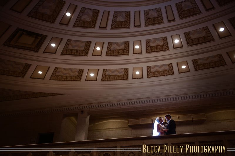 Bride and groom in silhouette on balcony of Temple Israel Minneapolis