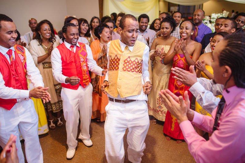 Ethiopian wedding groom dancing at reception in gold vest
