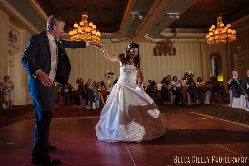 groom spins bride out during first dance at st paul hotel wedding reception mn