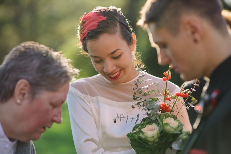 bride shows cabbage bouquet to guests at small wedding