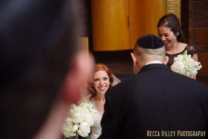 bride seeds groom through crowd of people at ketubah signing Beth El Synagogue in St Louis Park MN