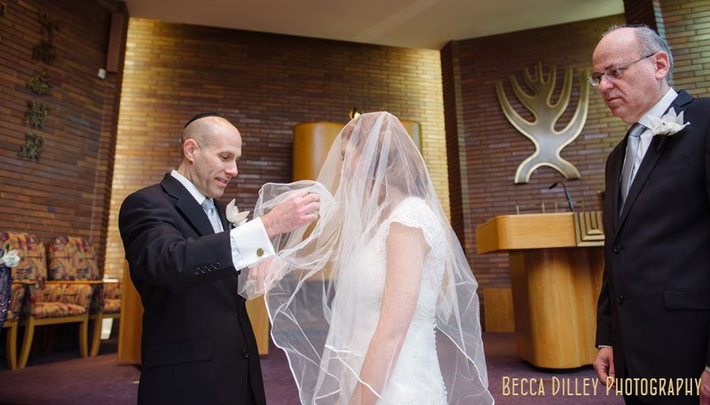 groom puts bride's veil over face