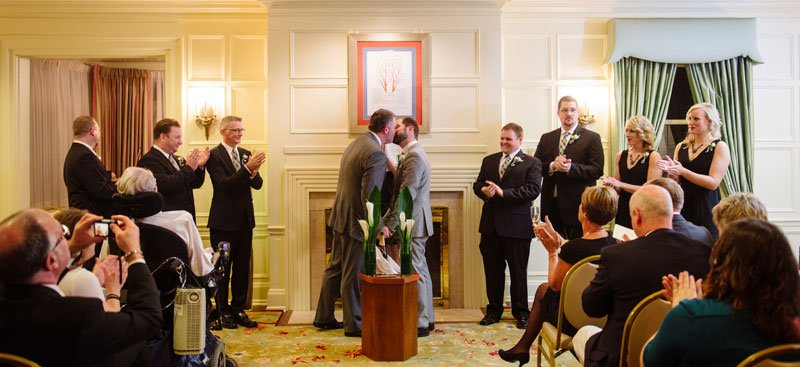 two grooms kiss after wedding at st paul college club wedding mn