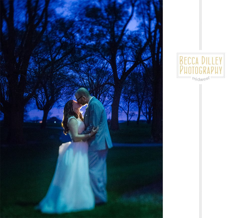 bride and groom at night with blue trees of golf course behind them