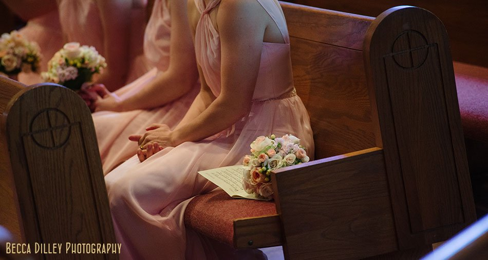 bridesmaids sit in pews for St Maria Goretti church wedding madison wi