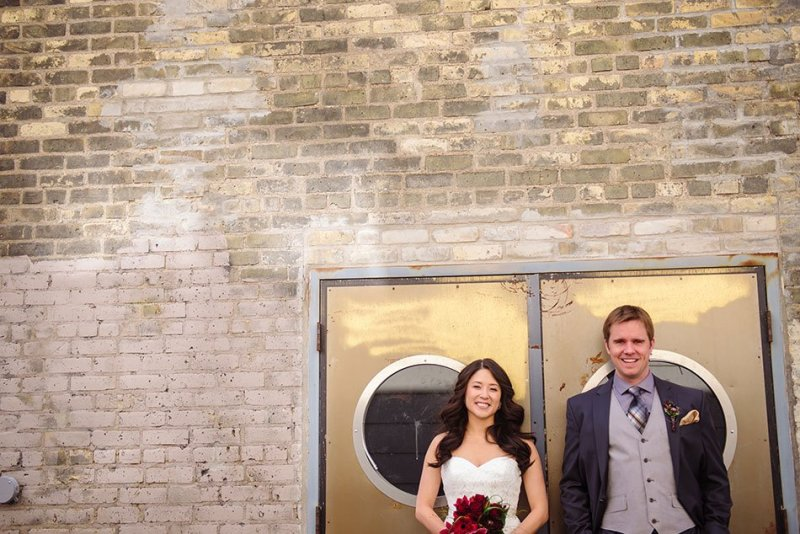bride and groom in front of brick wall of Varsity Theater wedding Minneapolis