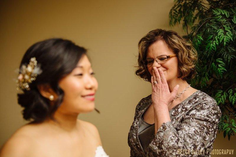 brides mom looks on as bride gets dressed