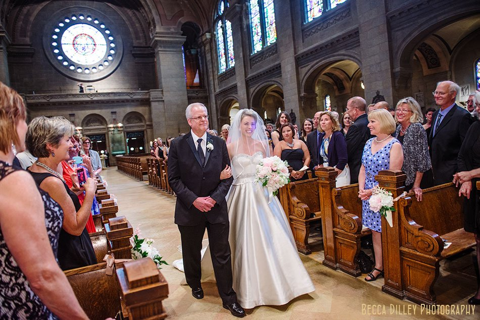 bride and father walk down aisle for basillica wedding minneapolis