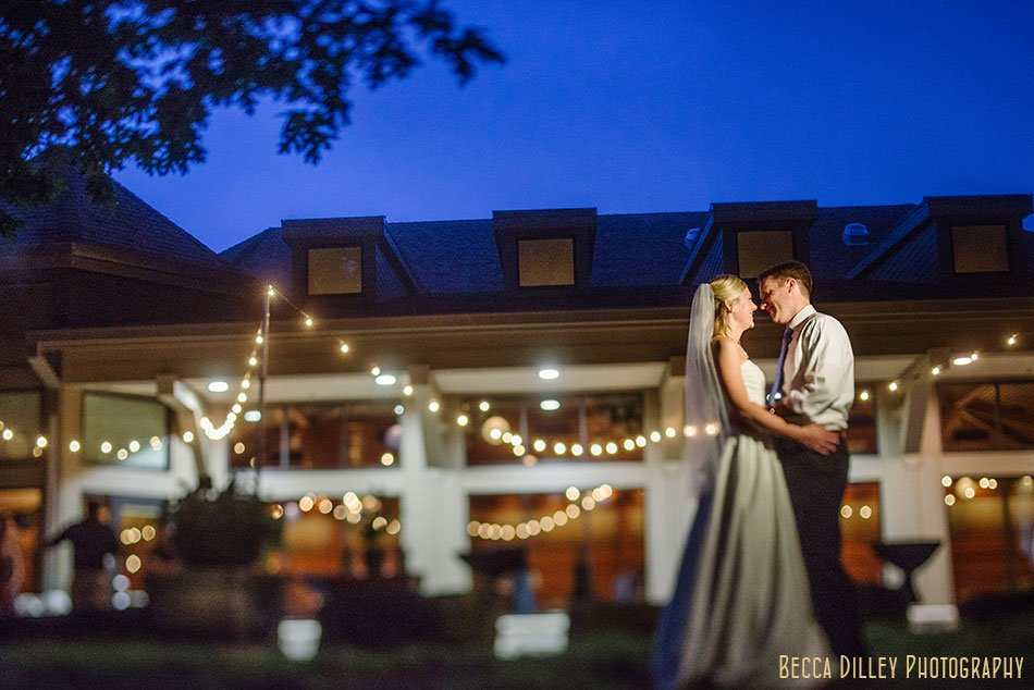 bride and groom embrace in front of lights at silverwood park wedding minneapolis