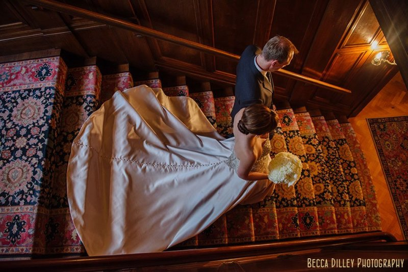 bride and groom going down stairs with long train minneapolis wedding at gale mansion