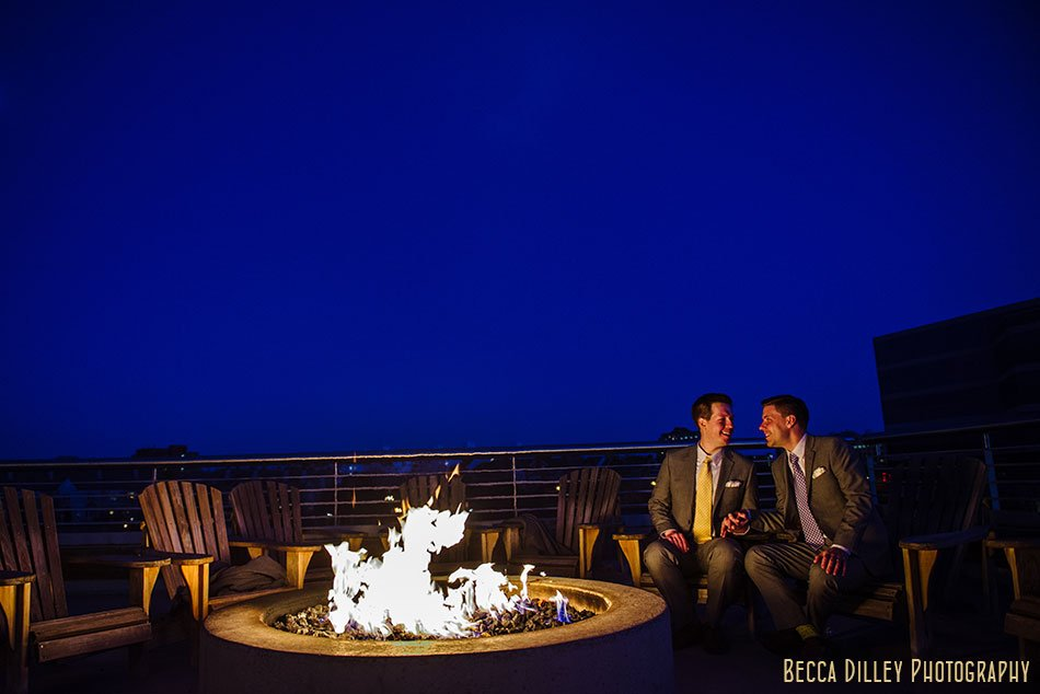 two grooms by fireplace pinstripes