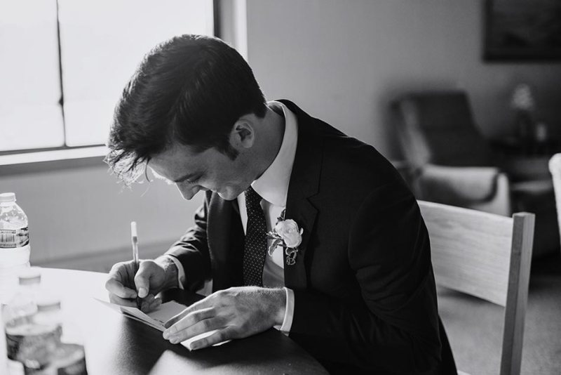 groom writes vows in church before ceremony for comfortable wedding photography