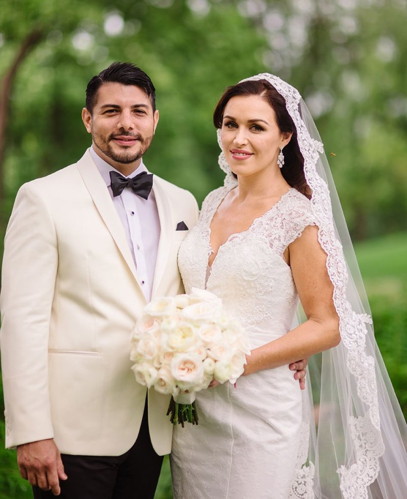 groom in white tux and bride with lace veil smile at camera outside the Wayzata country club