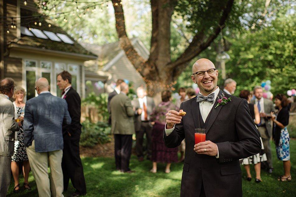 groom with cocktail White Bear Lake Backyard Wedding