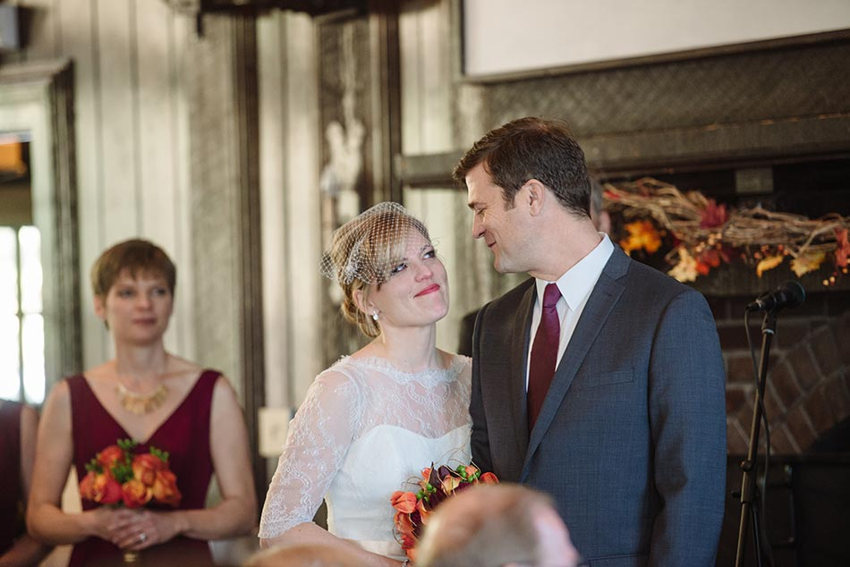 bride smiles at groom during ceremony Theodore Wirth Wedding Minneapolis